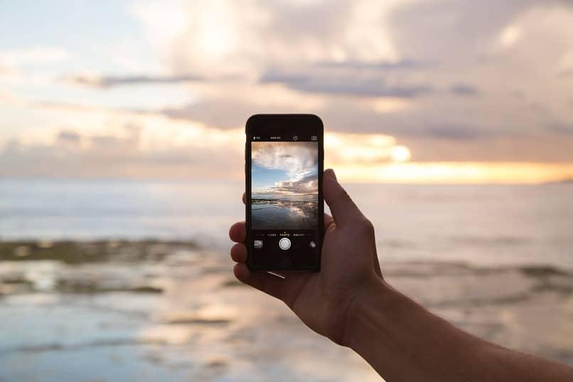 persona sosteniendo un movil en una playa