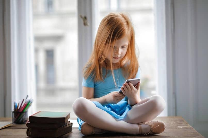 nina sentada con el celular
