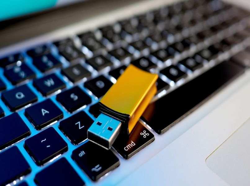 pendriver amarillo colocado encima laptop gris teclas negras letras blancas