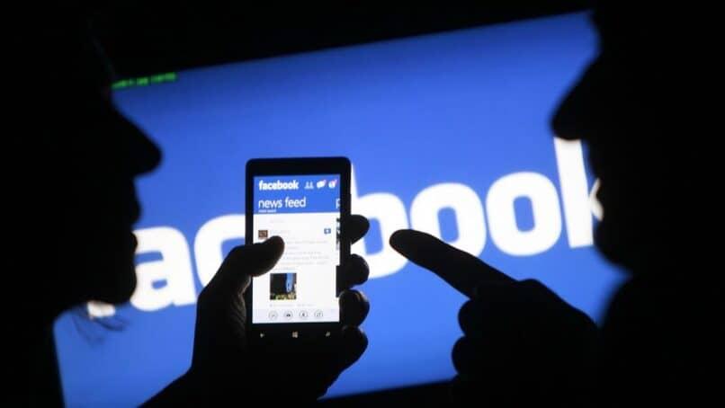 personas sosteniendo un movil con el logo de facebook de fondo