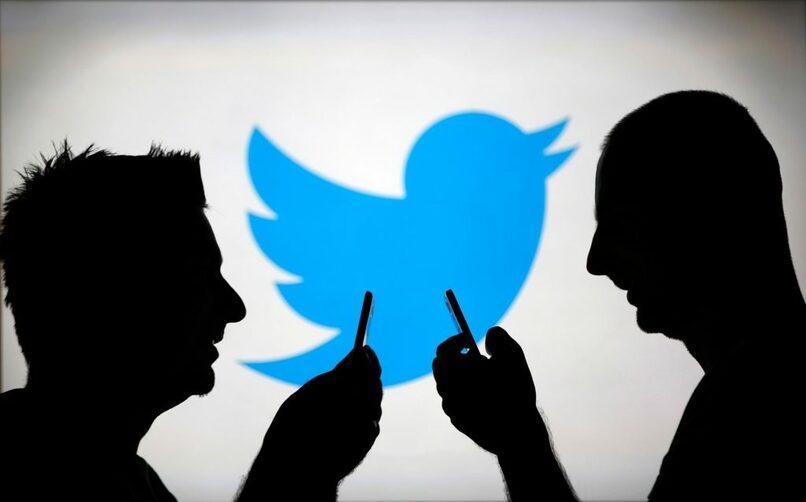 sombras de sujetos con logo de twitter en el fondo