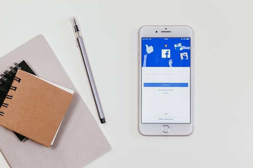 telefono blanco con facebook abierto