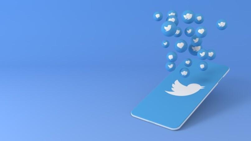 telefono con logo de twitter en pantalla y pequeños iconos flotando