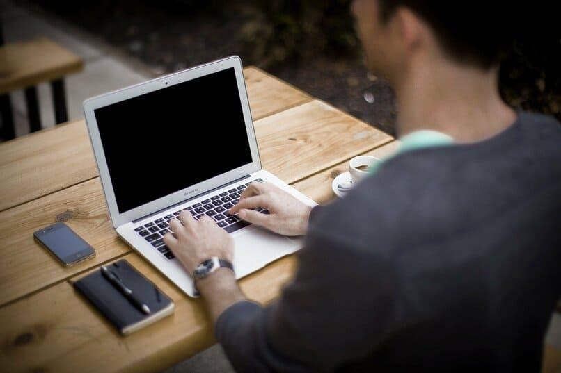 chico escribiendo en una laptop