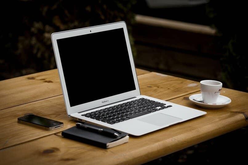 macbook color plateado sobre una mesa de madera