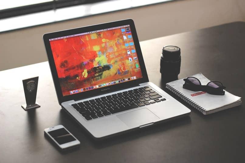 mac abierta sobre una mesa de color caoba