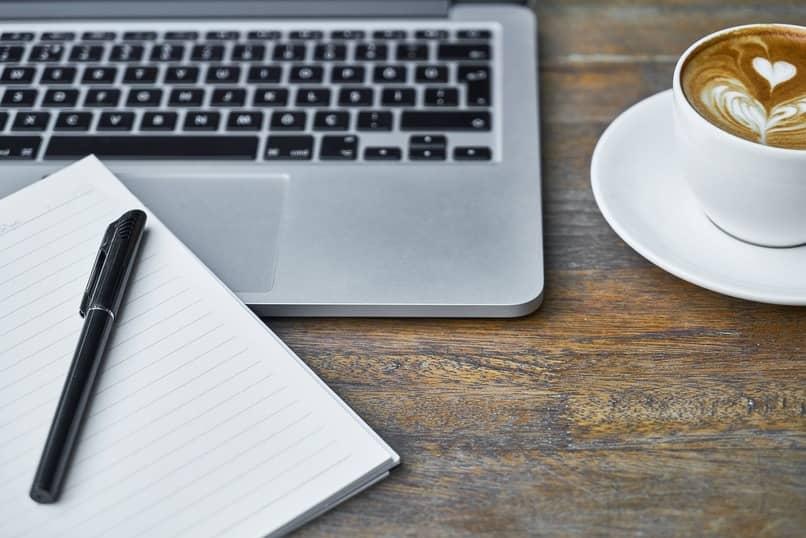 pc junto a una libreta y una taza de cafe