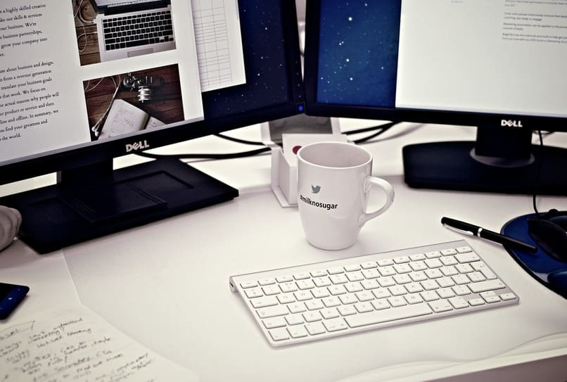 monitores de pc junto una taza de cafe