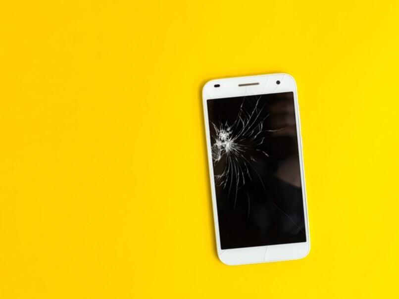 movil blanco con pantalla rota sobre fondo amarillo