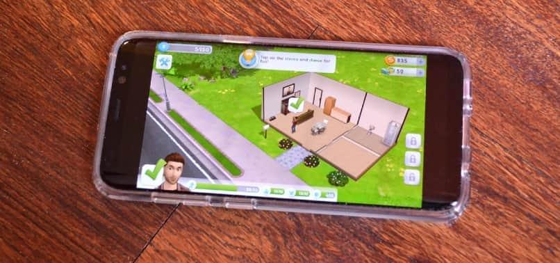 juego the sims mobile en smartphone negro