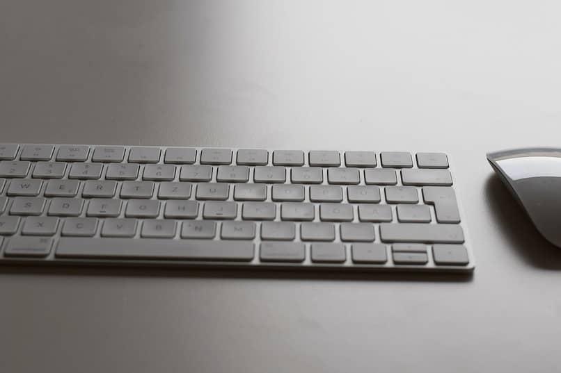 teclado de pc junto un mouse sobre una mesa