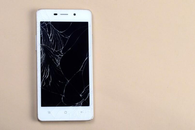 telefono blanco con la pantalla partida sobre mesa marron