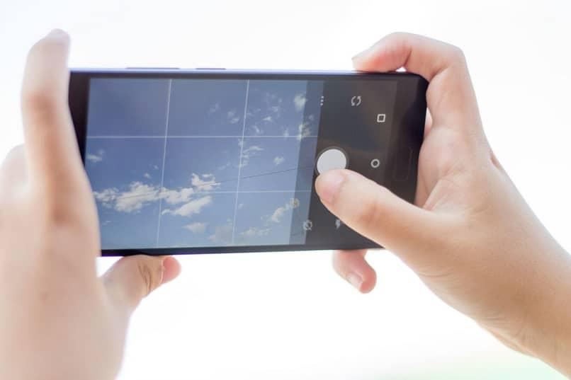 manos sosteniendo movil foto cielo