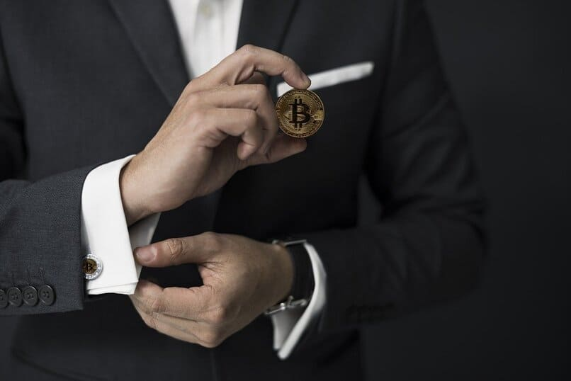 hombre sosteniendo una moneda de bitcoin