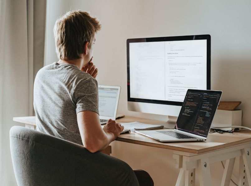 persona manipulando pc de escritorio en silla negra
