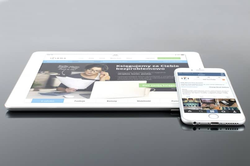 tablet y iphone blanco en superficie gris