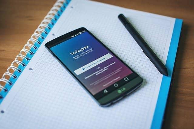 Móvil con el inicio de Instagram sobre una libreta