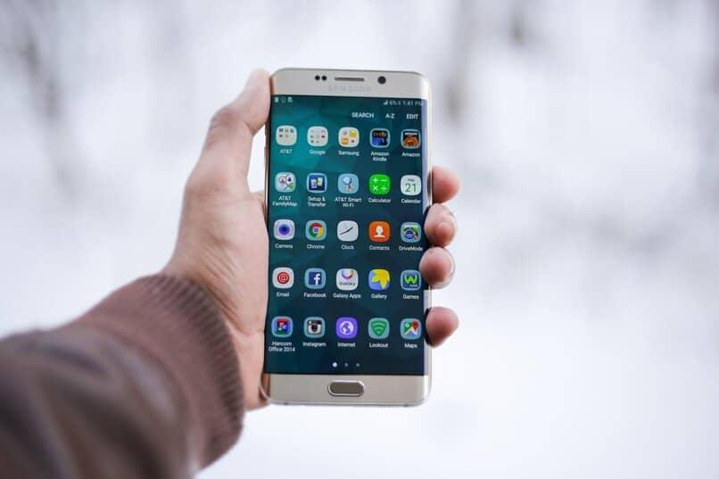 Hombre sosteniendo su móvil con diversas apps en su pantalla