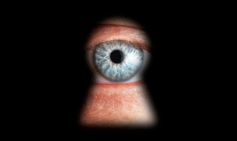 ojo azul espiando por cerradura puerta