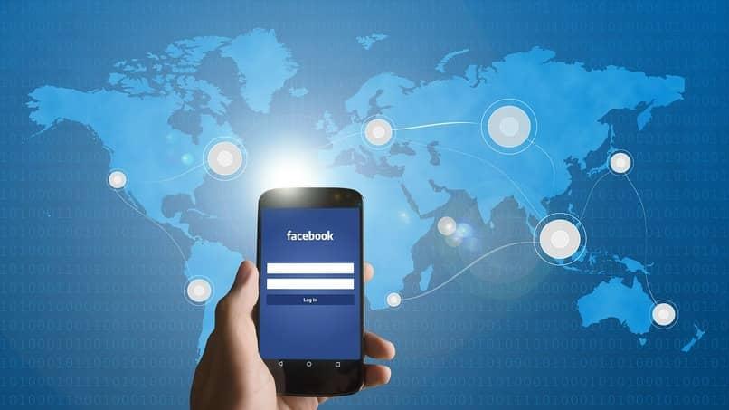 dispositivo movil utilizando facebook con mapa del mundo de fondo