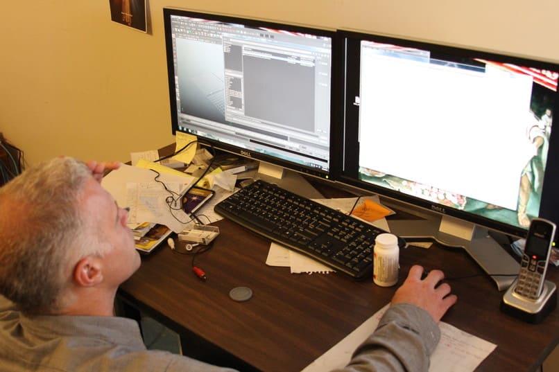 hombre utilizando dos ordenadores