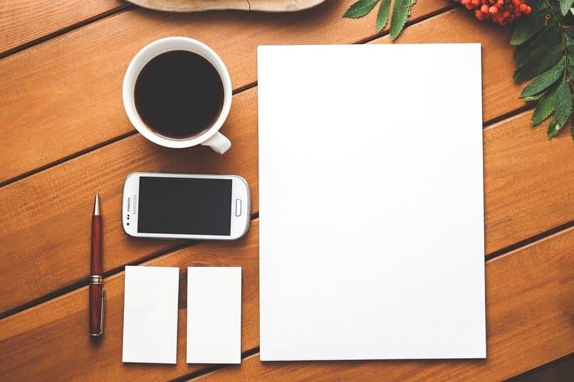 movil color blanco junto a una taza de cafe