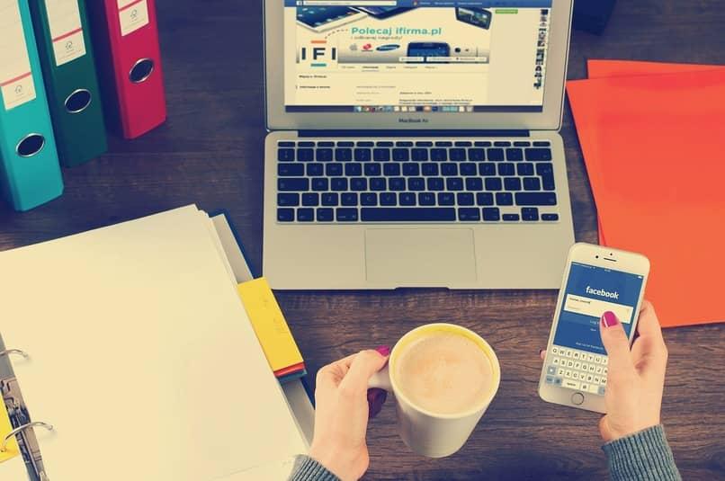 mujer sosteniendo un movil con la pagina de facebook en su pantalla