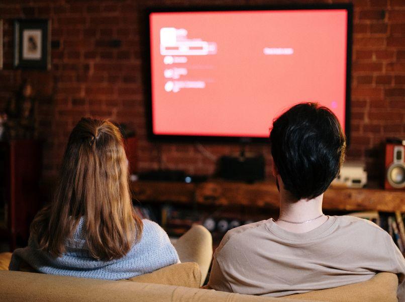 pareja sentadas viendo tv